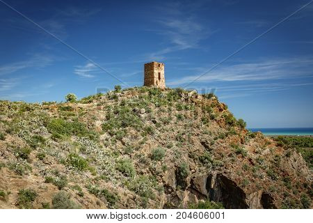 Wide angle shot of antique stone tower over hill near sea