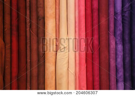 background of very colorful fabrics in the dress shop for dresses or trendy tablecloths