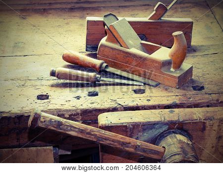 workbench with two planes and two chisels and a vice with vintage effect