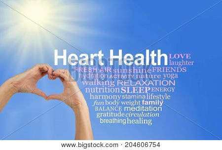 Look After and Love your Heart Word Cloud - pair of hands making a heart shape with a HEART HEALTH word cloud to the right  on a blue sky and sun burst background