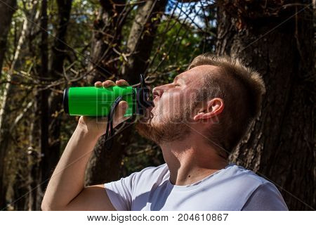 A fitness man after running in nature drinks his protein from the sheik acts as a refreshing and gets the strength