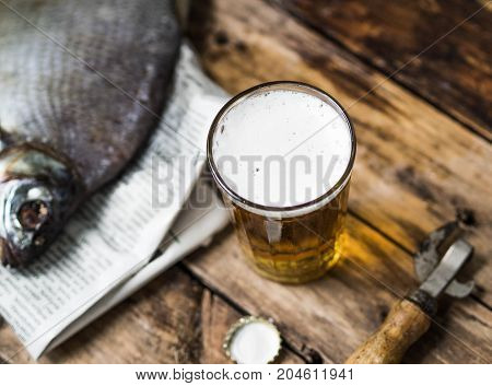 A glass beaker with beer next to a large dried fish bream on an old wooden background