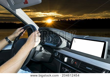 Male hands holding car steering wheel. Hands on steering wheel of a car driving near palm field. Man driving a car inside cabin. Multimedia system isolated white blank screen. Copy space