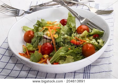 fresh garden salat with tomato and carrot in a white bowl