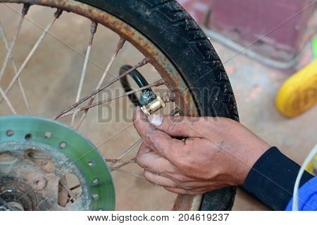 a repairing man fill up the air into the motocycle wheel