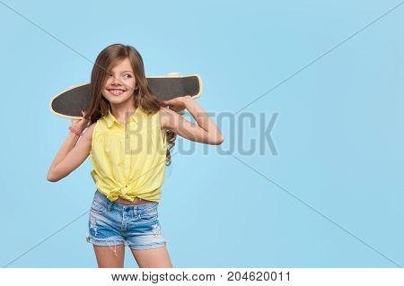Smiling young girl holding cruiser board on shoulders wearing yellow blouse jean shorts looking away posing.