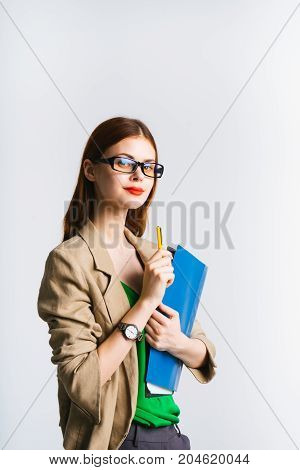 A modern serious business lady, confident, looks at the camera, holds documents. Young teacher intern