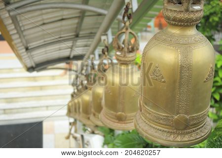 View of a row golden bells in buddhist temple ThailandAsia