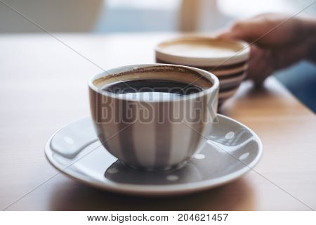 Closeup image of Americano coffee cup and woman's hand holding latte coffee cup on vintage wooden table in cafe