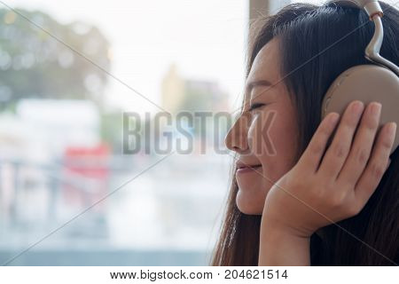 Closeup image of a beautiful Asian woman close her eyes and enjoy listening to music with headphone in modern cafe with feeling relax and happy
