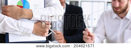 Female arms hold silver pen and pad with financial statistics at workplace closeup. White collar check money papers school or college homework exercise internal Revenue Service inspector concept