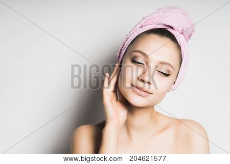 Beauty face woman touch her clean skin face. Girl in towel