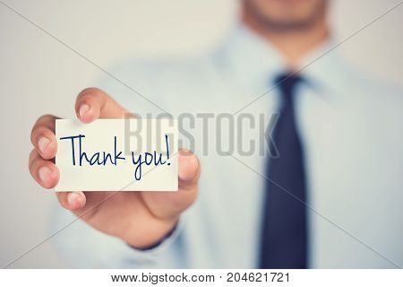 Thank you word on card hold by man