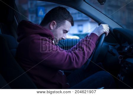 Man driving car and falling asleep at the wheel