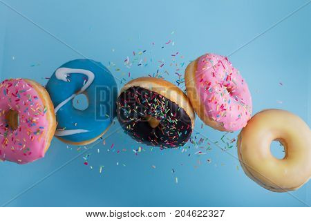 flying doughnuts - mix of multicolored sweet donuts with sprinkel on blue background