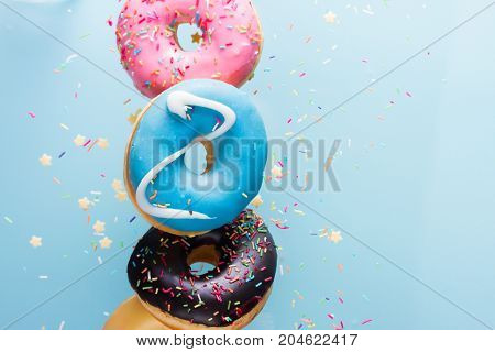 flying doughnuts border - mix of multicolored sweet donuts with sprinkel on blue background