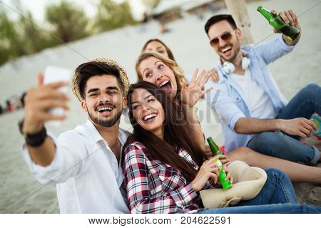 Happy young group of people taking selfies on beach in summer