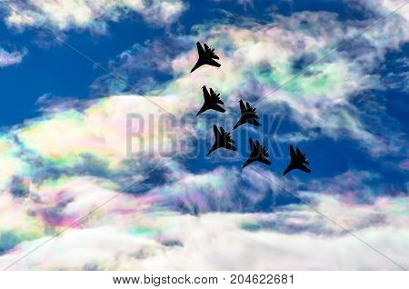 Fighter Jet Group Flies In The Clouds And Iris Multicolored Sky