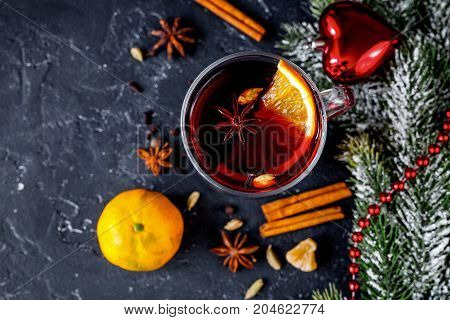 Christmas mulled wine with spices in cup on dark background top view