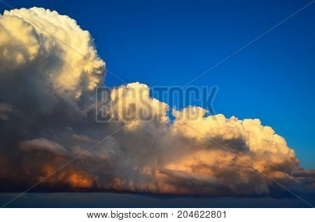 Grandiose Huge Powerfully Cumulus Clouds At Sunset In Blue Sky