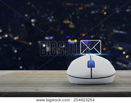 Mail flat icon with wireless computer mouse on wooden table over blur colorful night light city tower Contact us concept