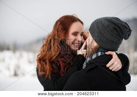 Redhead woman touching nose of her boyfriend