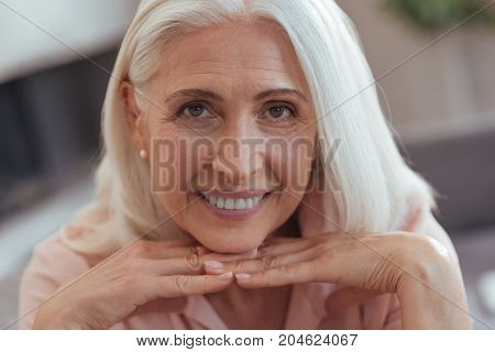 Emotional wave. Prtraoit of a cheerful aged woman smiling and holding her chin on the hands while lookign at you