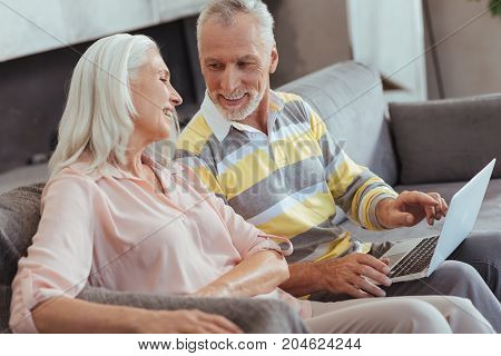 Eternal feeling. Cheerful lovign aged couple sitting on the couch and resting at home while using laptop