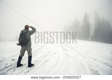 Man with backpack in the winter mountains peers into the foggy distance. Winter landscape. The concept of freedom, travel and choice of ways.