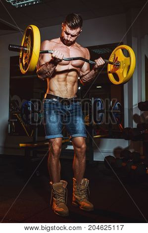 Athletic Young Man Doing Exercises With Barbell In Gym. Handsome Muscular Bodybuilder Guy Is Working