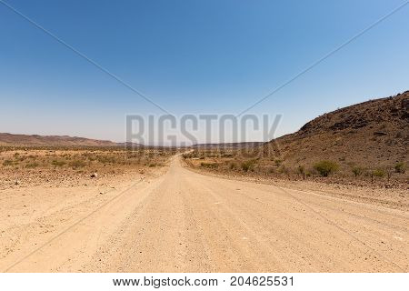 Gravel 4X4 Road Crossing The Colorful Desert At Twyfelfontein, In The Majestic Damaraland Brandberg,