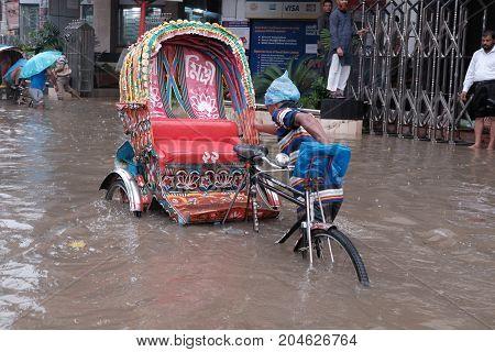 Dhaka, bangladesh, september 2017- heavy raining cause water logg and bangladeshi residents wade through water loggroad located at motijhil area in dhaka city in bangladesh taken on 12 september 2017.