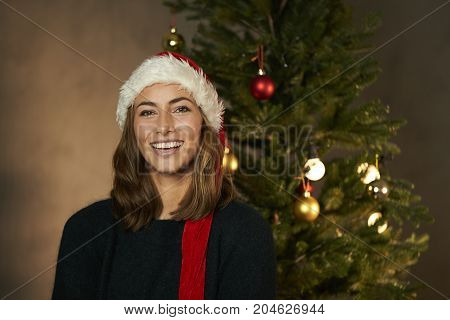 Laughing Christmas beauty in Santa hat by tree portrait