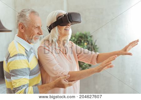 I will help you. Positive aged woman testing VR glasses while her loving husband standing behind and supporting her