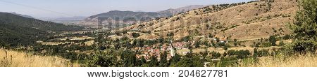 View of the mountains, the village and the mountain road on a sunny day  (northwest Greece, Macedonia)