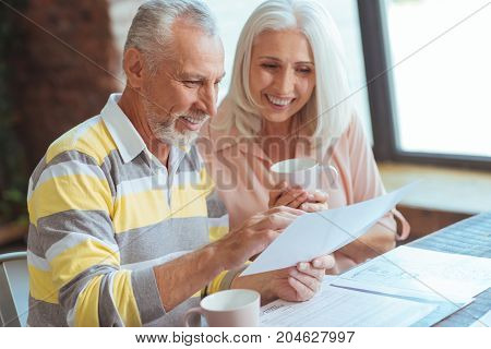 Open up the market. Positive senior couple being involved in paperwork and sitting at home while discussing their business matters