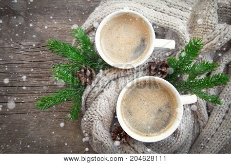 two cups of coffee on a wooden table. cozy warm knitted blankets, branches and cones of Christmas tree. snow Christmas winter background still life. hot chocolate cocoa cup. top view. place for text.