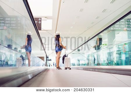 Young teen woman with hand luggage,suitcase carrying on escalator in international airport terminal. Traveler on vacations
