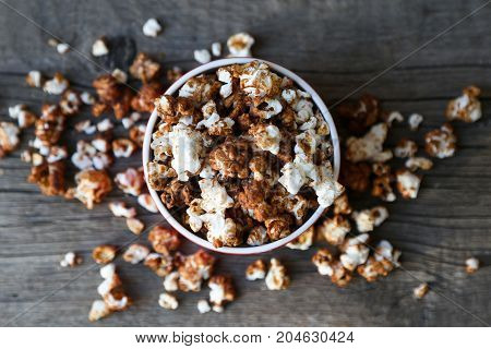 chocolate caramel popcorn on the wooden background.