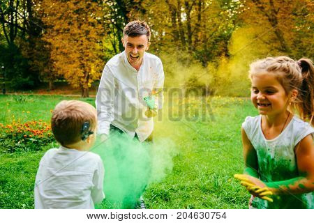 father doughet and son playing with holi paints in city park