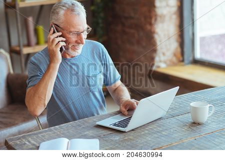 Busy days. Positive delighted elderly man talking on phone and using his laptop while being involved in work at home