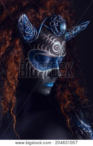 Fabulous female from fairytale with blue black body art corset and horns