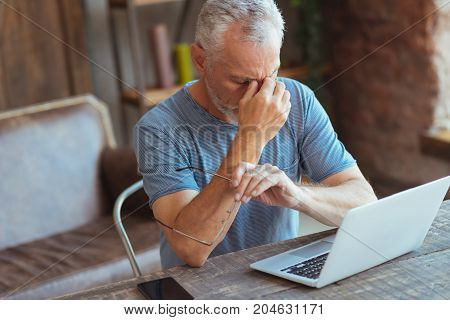 A bit tired. Retired cheerless man sitting at the table and using his laptop while sufering from a headache