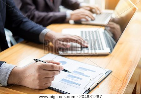 Business man analysed report of profit finance data graph document in his office