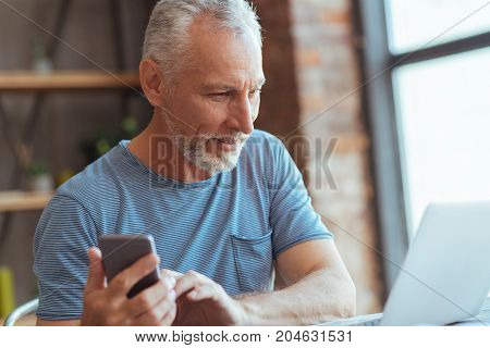 Modern user. Positive aged man sitting at the table and using his laptop while holding a smart phone