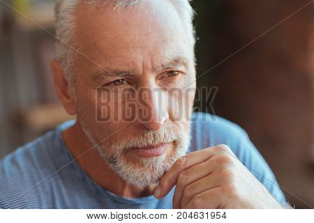 Smart look. Portrait of a thoughtful aged man holding his hand on the chin and looking aside while being involved in thoughts