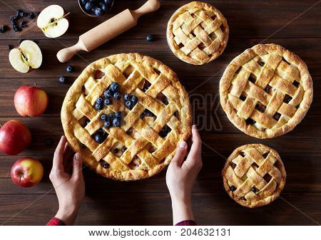 Apple pie on the wooden table with apples, raisins, blueberry and rolling pin. Hands in the frame. Traditional dessert for Thanksgiving. Flat lay bakery food background. Dark food photo.