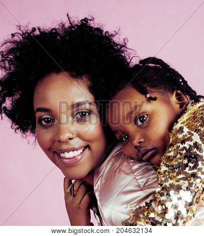 young pretty african-american mother with little cute daughter hugging, happy smiling on pink background, lifestyle modern people concept close up
