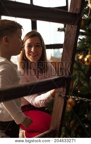 Happy smiling family decorating Christmas tree together. Young loving mother and her child having fun at home. Merry Christmas and Happy holidays.