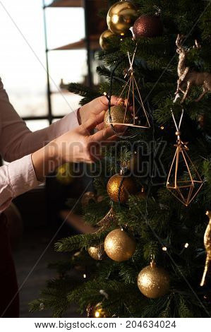 Closeup of female hand decorating Christmas tree with golden toys. Merry Christmas and Happy Holidays